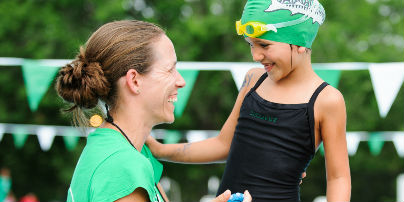Coach and swimmer smiling